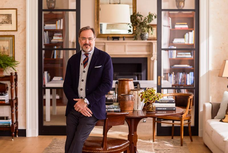 Gil Schafer '84, wearing a tie, vest, and jacket, leans on a chair, framed by windowed doors in front of a fireplace