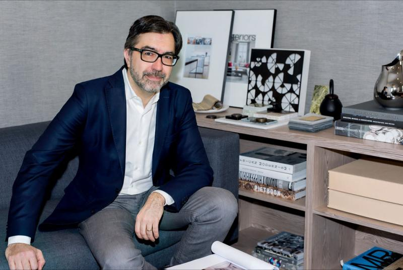 Jean Gabriel Neukomm '90, wearing glasses and a blue blazer, sits on a low gray couch next to a bookshelf that's full of art books and prints