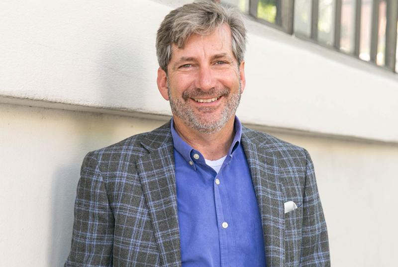 A portrait of Mark Miller '84, wearing a blue shirt and a gray and blue checked blazer