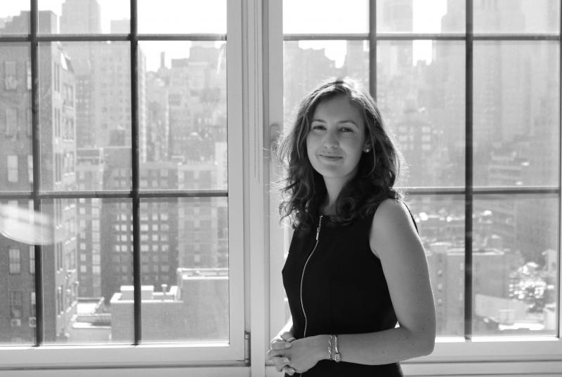 A black and white portrait of Sarah Astheimer '01, standing in front of large windows overlooking Manhattan