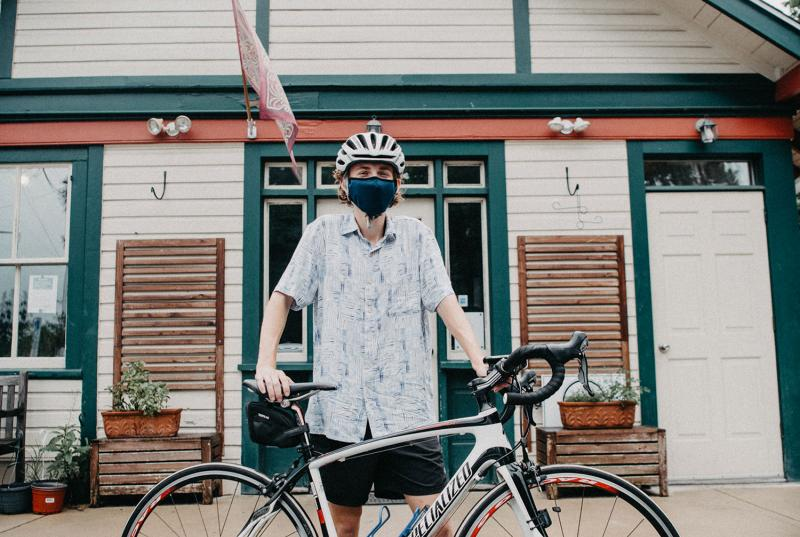 Matthew Katz '22 wears a bike helmet and mask, standing with his bicycle in front of one of the vintage train stations on the Main Line