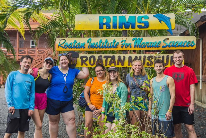 Kristen Whalen and her students in shorts and bathing suits standing in front of the sign for Roatán Institute for Marine Sciences