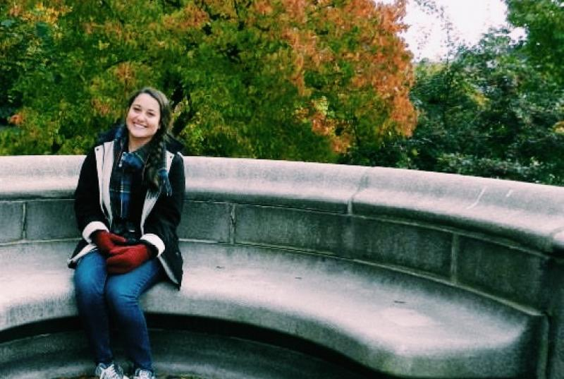 Kristen Andersen sitting on a stone bench in front of fall foliage