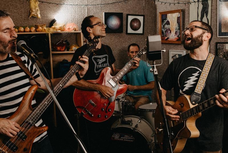 The band jams together in their practice space