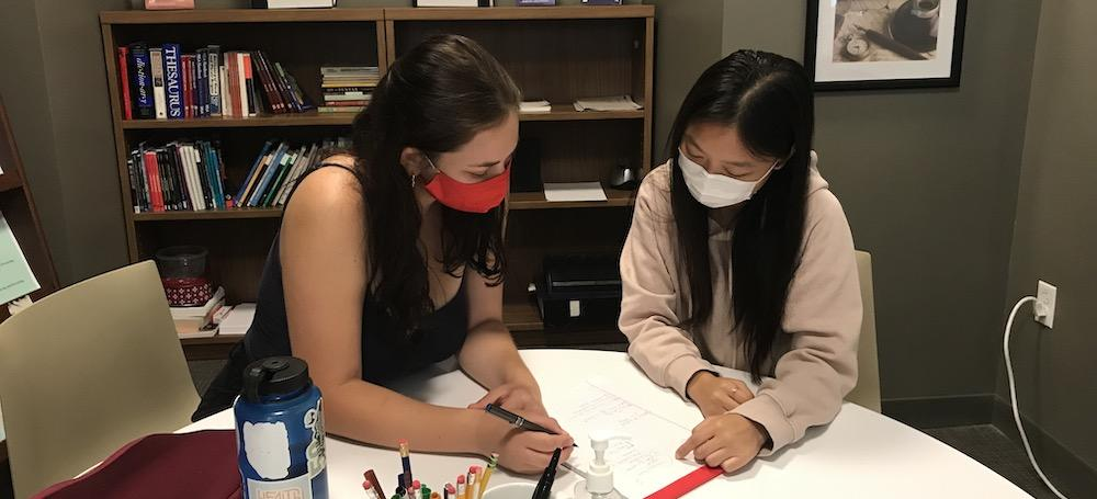 A peer tutor works with a student