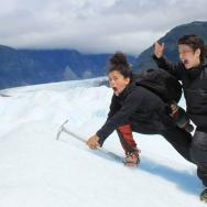 Two students climbing a snow-covered mountain and mugging for the camera
