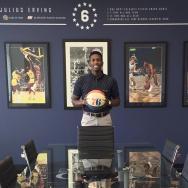 Tejan Walcott holding a Philadelphia 76ers basketball
