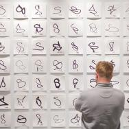 A wall covered with various interpretations of the letter S