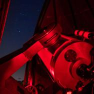 A student observing the night sky through a telescope