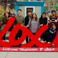 A group of students pose behind a sculpture in Philadelphia
