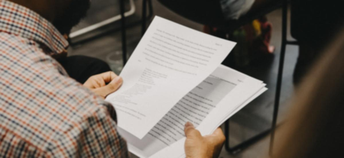 Student holding a stack of papers reviewing the content
