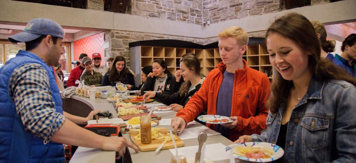Students enjoying different meats and cheeses.