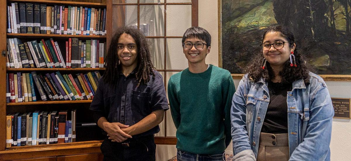 Three students pose with a new collection of diverse philosophy texts named in their honor