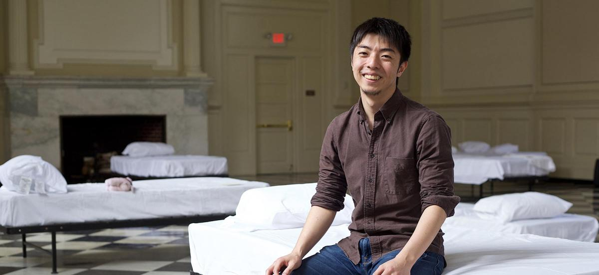 Yoshifumi Nomura sitting on a bed in Founders Hall