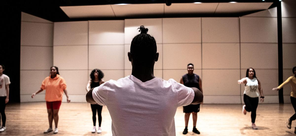 A dancer stands with back to the camera while leading other members in a Step dance routine