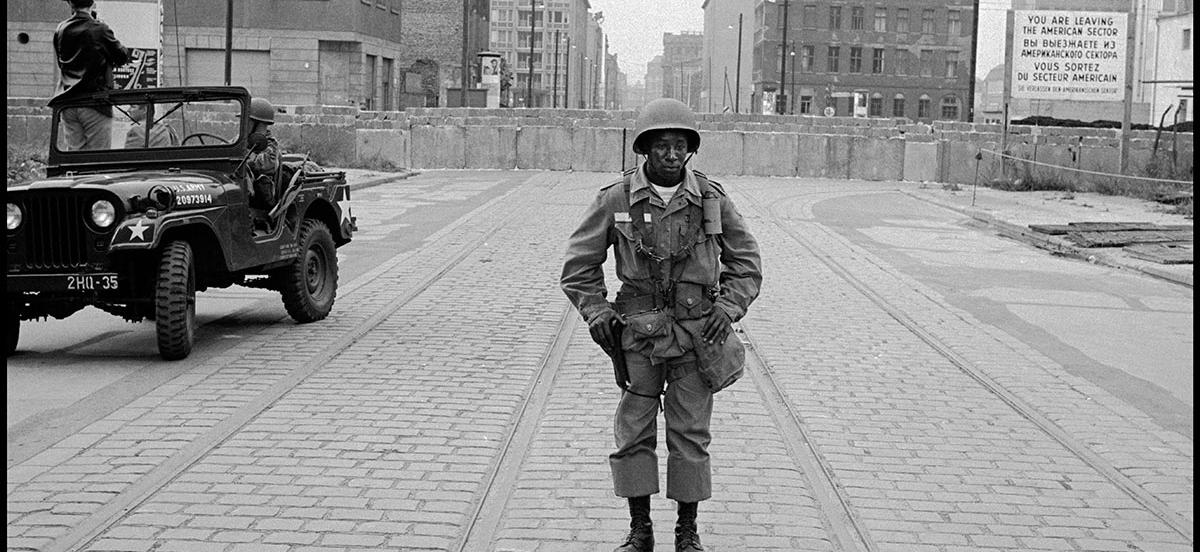 Photo of an American soldier standing with the Berlin Wall in the background