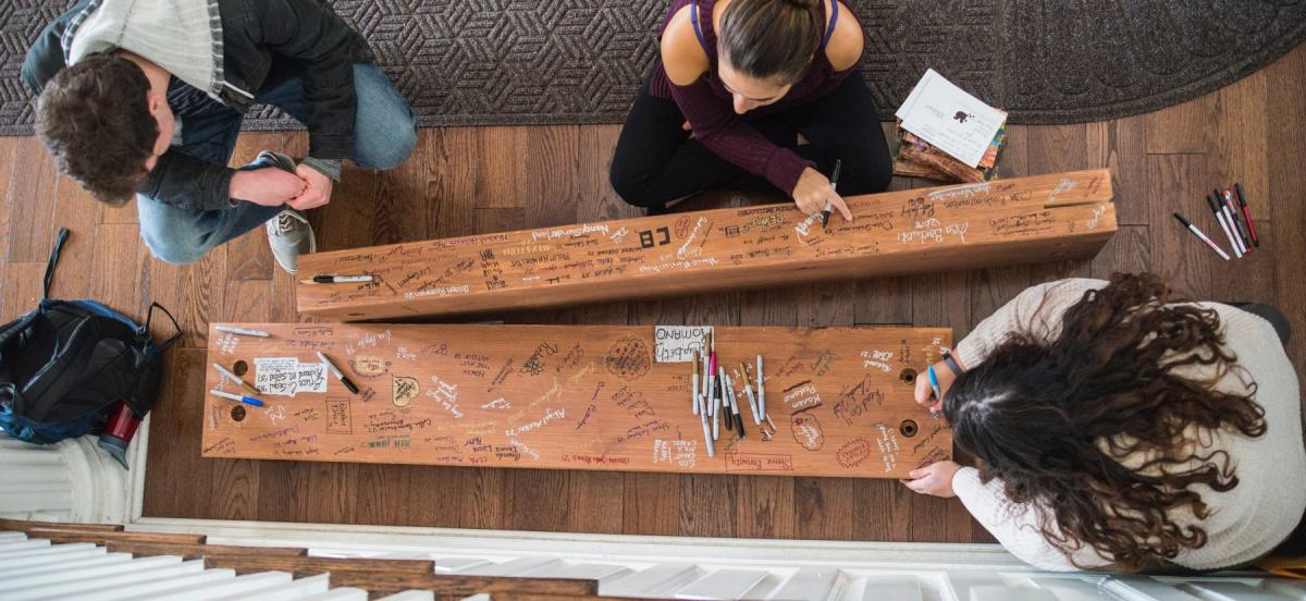 People signing wood beams that will be installed in the renovated library