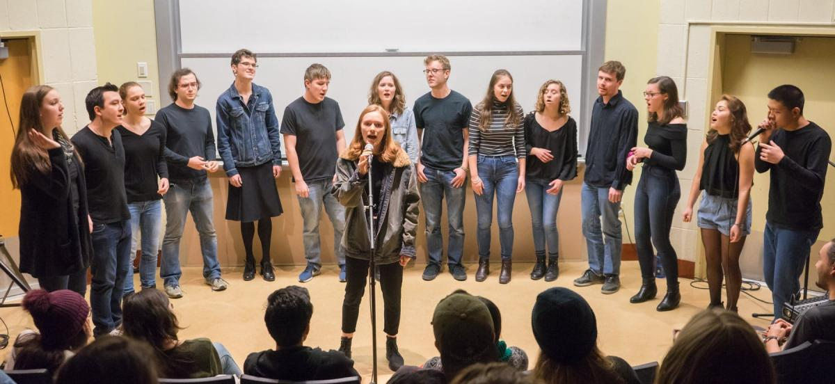 An acapella group performs with a woman singing solo in front.