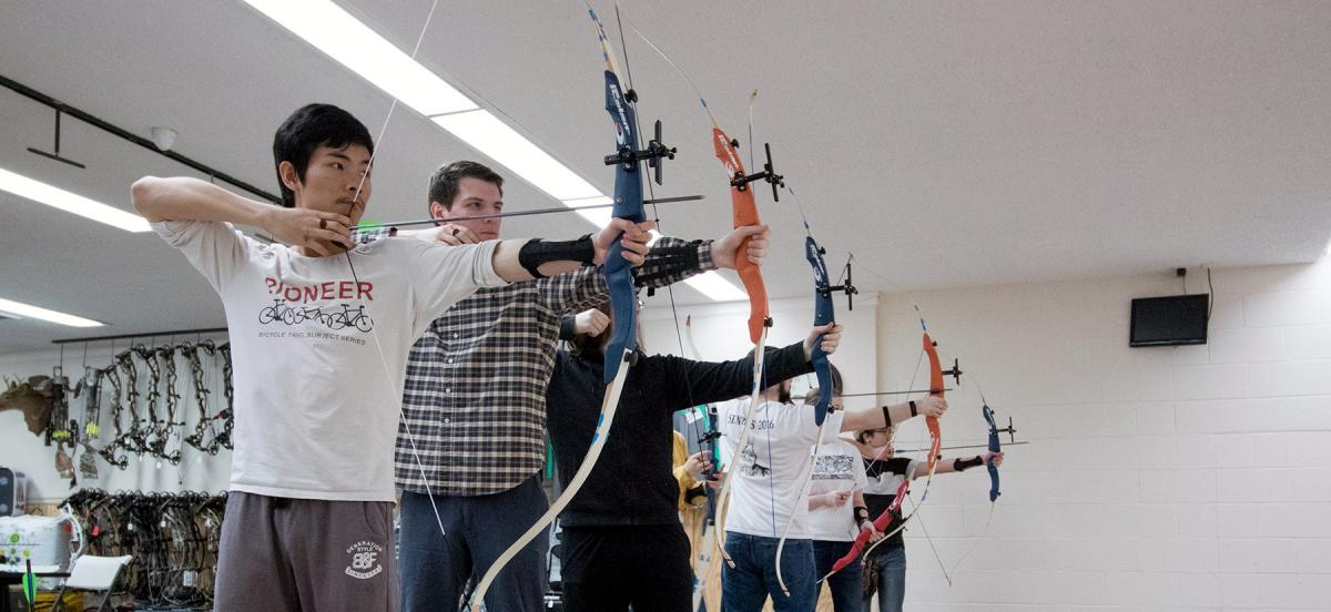 Students in a line with arrows nocked in compound bows