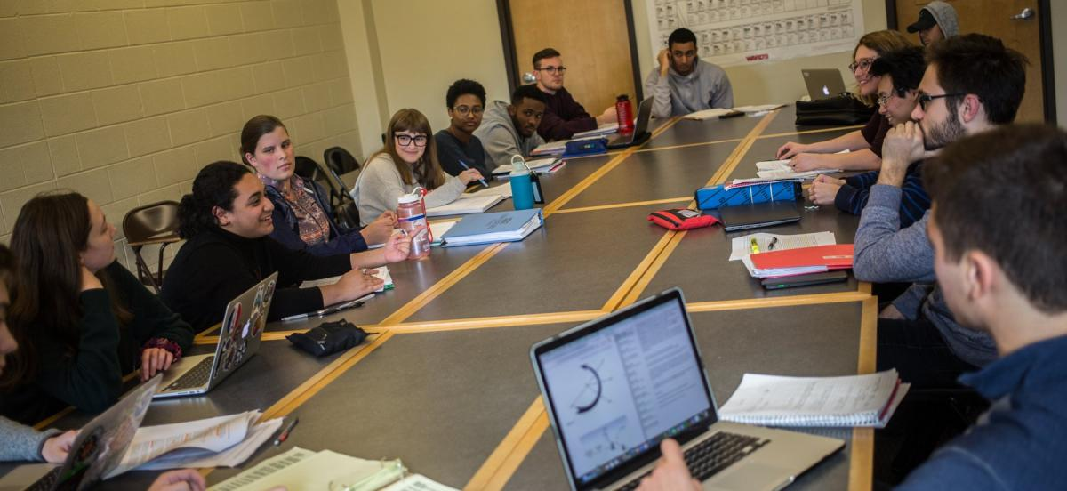 Students discuss a topic around a large table