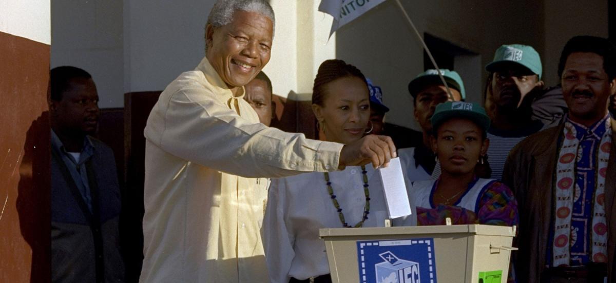 Nelson Mandela drops his ballot into a voting box