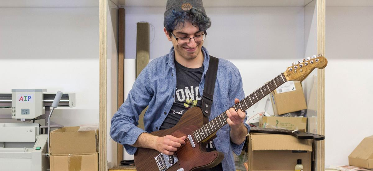 Micah Maben poses with a guitar created in VCAM's Maker Space