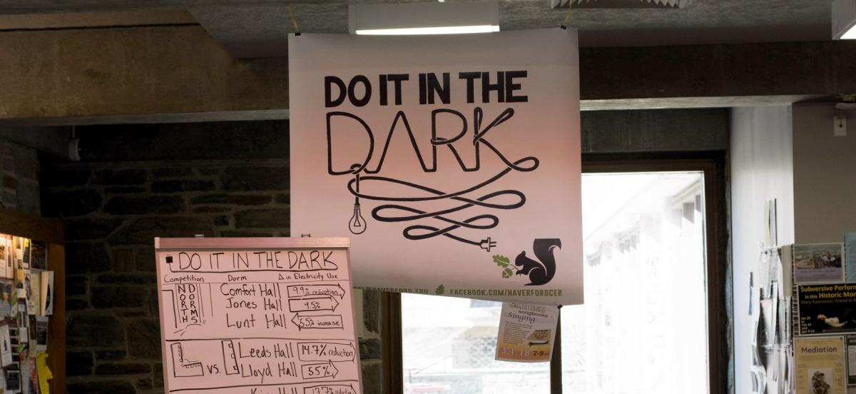 A Do It In The Dark banner hanging in the Dining Center