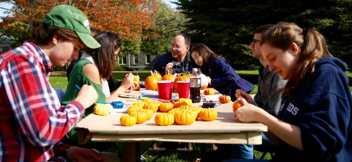 Family at table painting pumpkins
