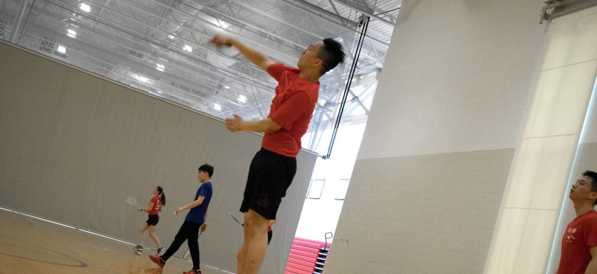 Man jumps in air playing badminton