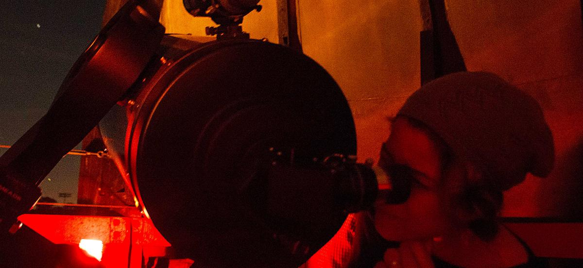 Person looking through a telescope