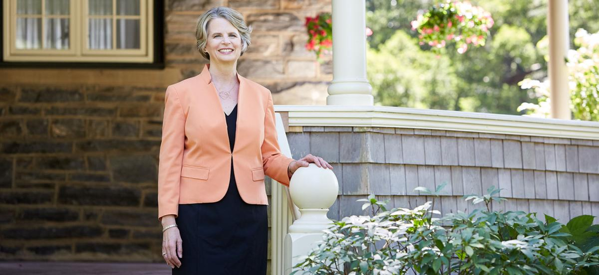 Woman in business suit stand outside of house