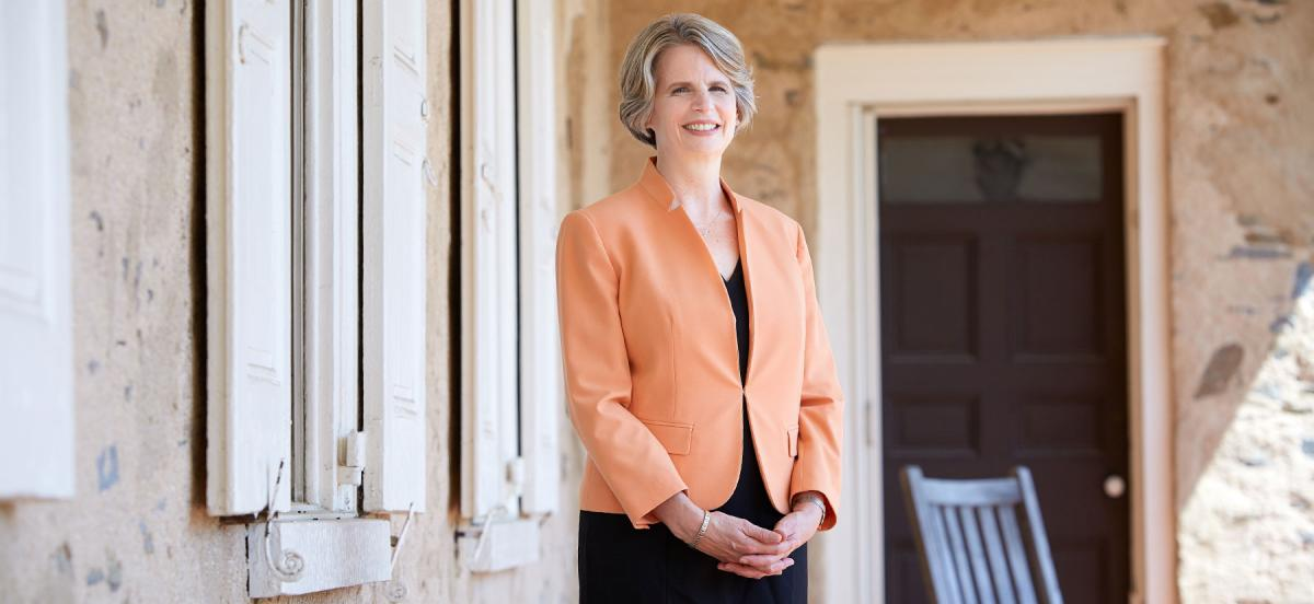 Woman in business suit stands on porch