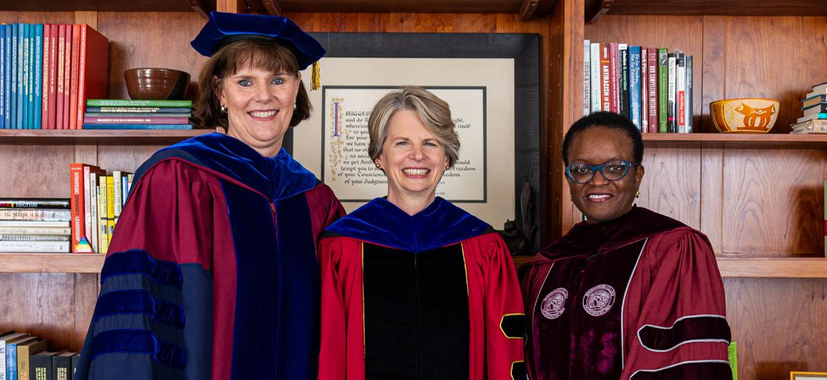 Three women in academic robes stand together in front of bookcases
