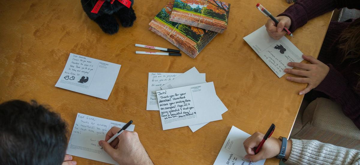 Students sign thank you post cards