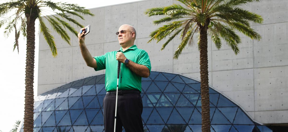 Blind man taking a selfie in front of a building and palm trees