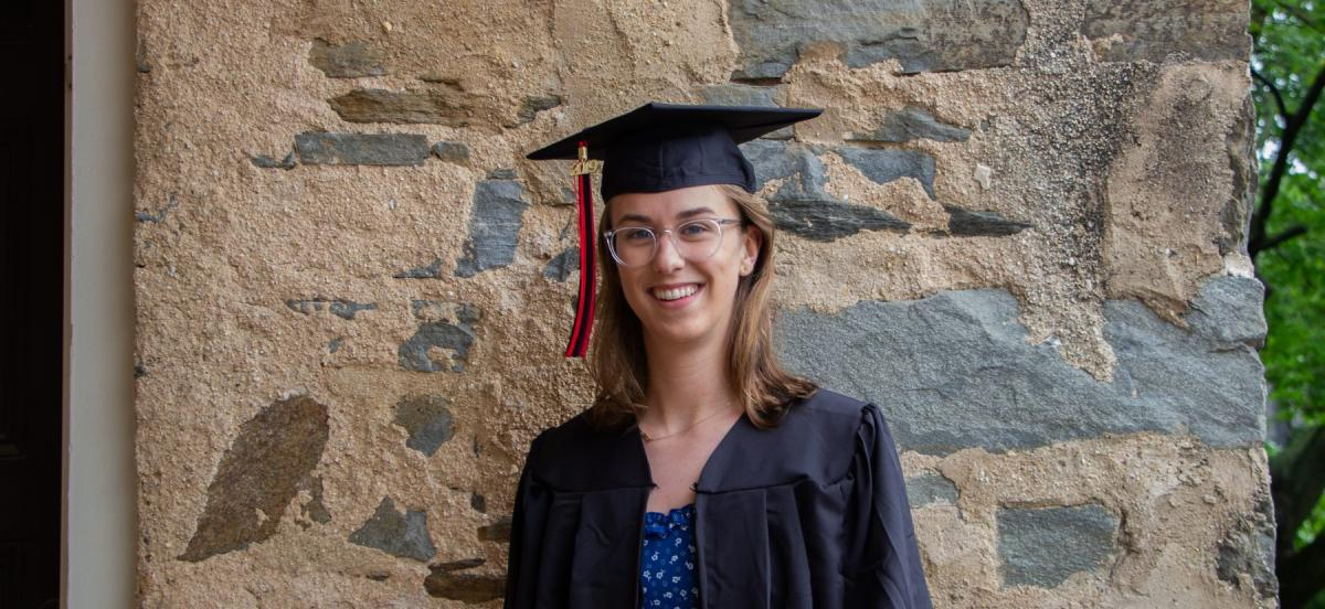 Woman in graduation gown smiles in front of stone wall