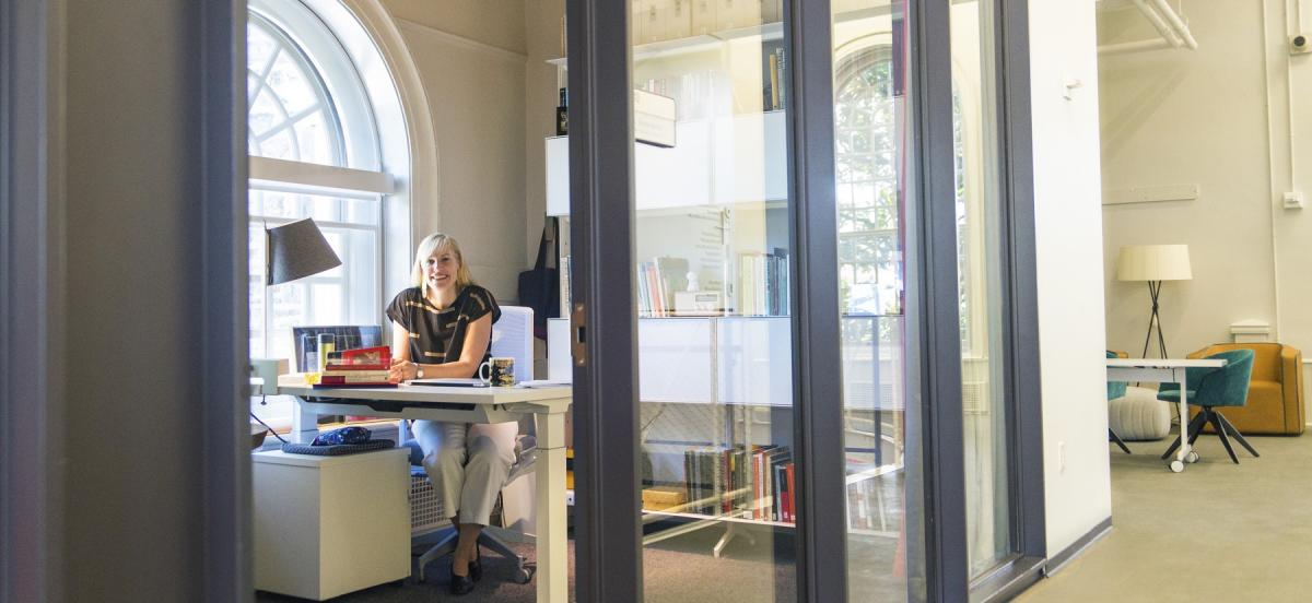 Erin Shoneveld seated within her glass-walled office in the VCAM