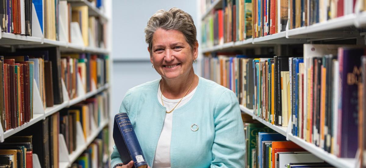 Woman holds a hardback book inbetween aisles of bookshelves