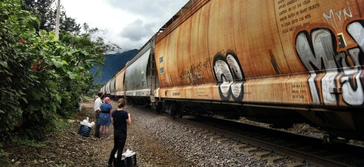 Migrants standing alongside of a passing train in Mexico