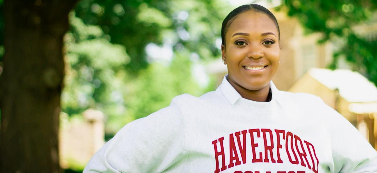 a woman stands in front of trees wearing a Haverford College sweatshirt.