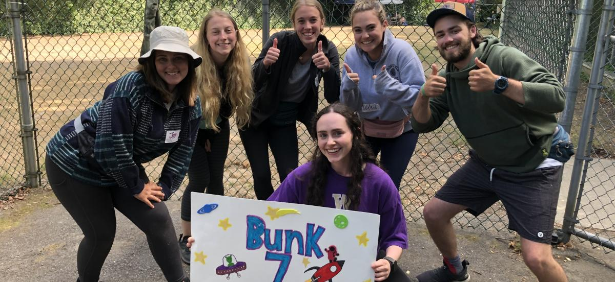 """Photo of Isabel Russak at the bottom holding a """"Bunk 7"""" sign with her co-counselors around her."""