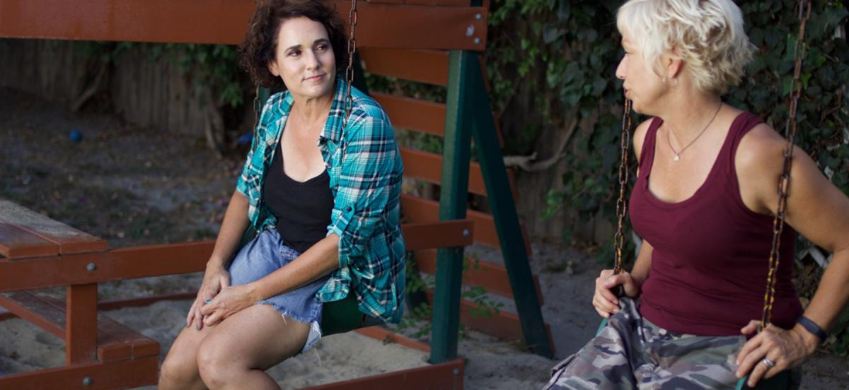 Colette Freedman in a scene from her movie Quality Problems, sitting on a swingset with another woman