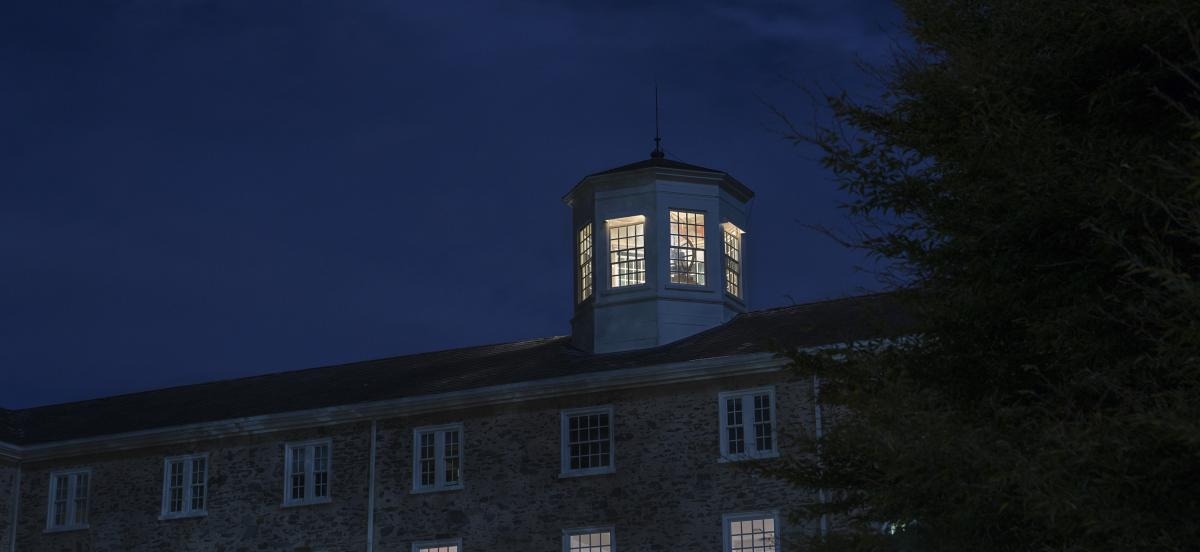 Founders Hall at night with the cupola lit up