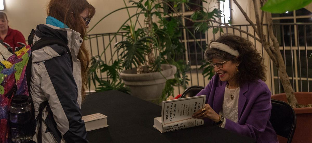 """Shoshana Zuboff signs a student's copy of her book, """"Surveillance Capitalism"""" at an event at Haverford College"""