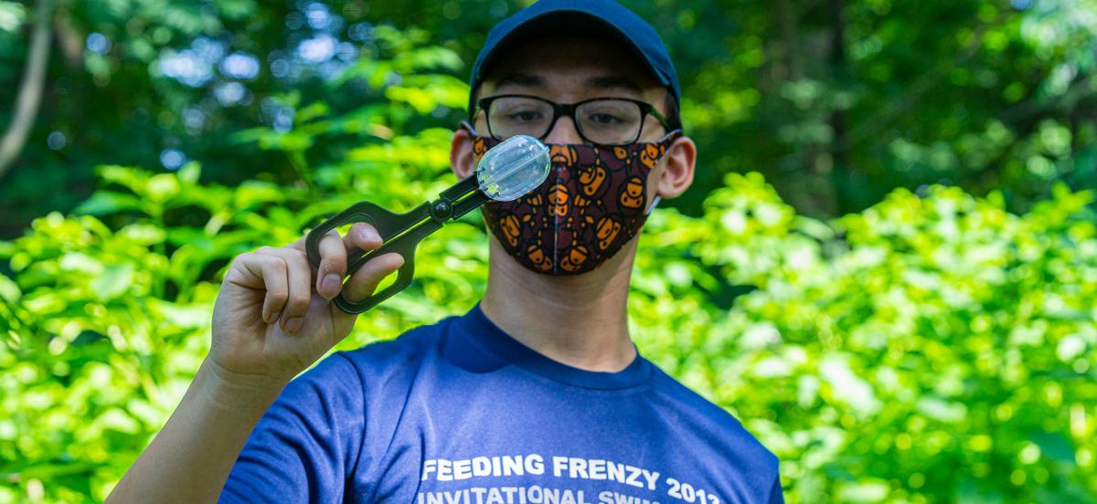 Theo Bi n wears a mask on the Nature Trail while handling a spotted lanternfly specimen