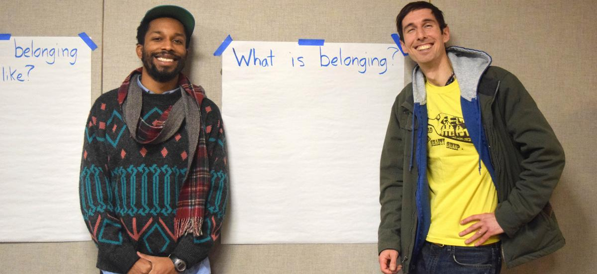 "Sterling Duns and Caselli Jordan stand in front of a large piece of paper asking what ""belonging"" is"
