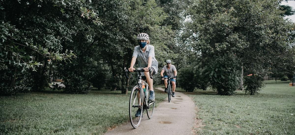 Matthew Katz '22 wearing a helmet and mask bikes part of the Main Line Greenway