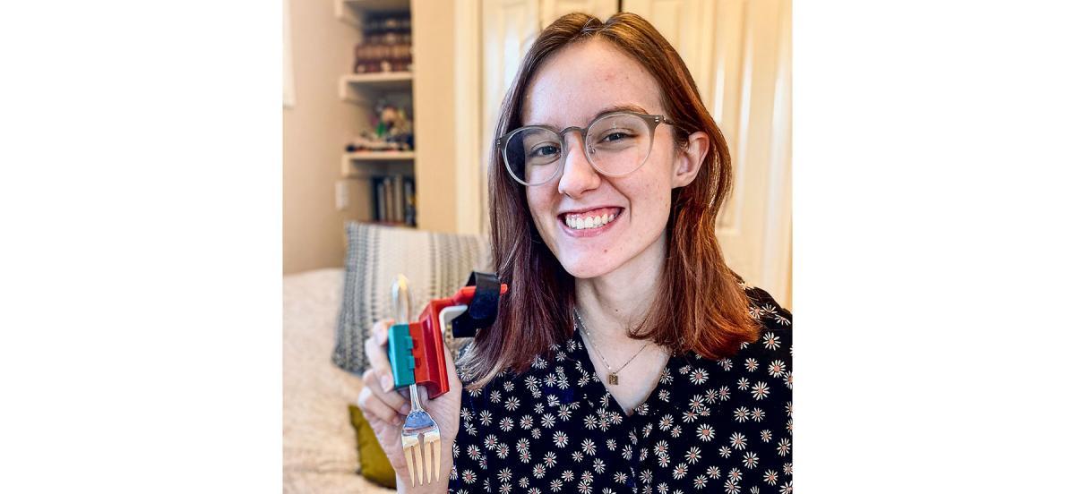 August Muller holds her utensil-holding prosthesis prototype