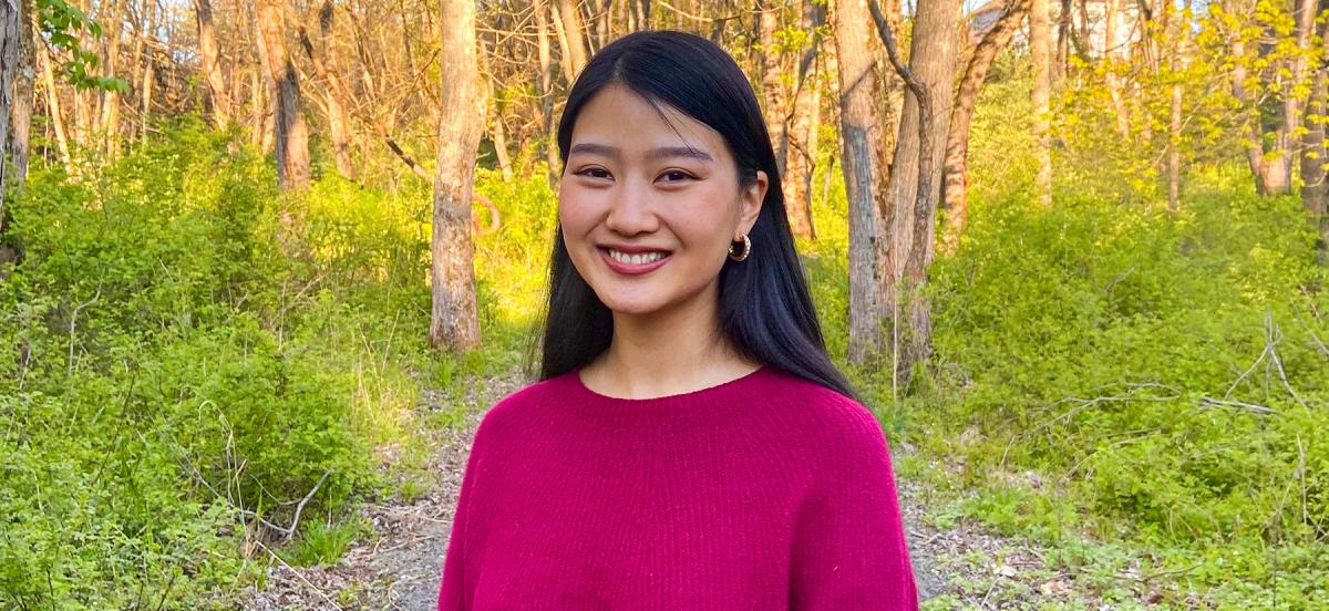 Claire Cai '21 smiles, wearing a pink sweater, on the Nature Trail.