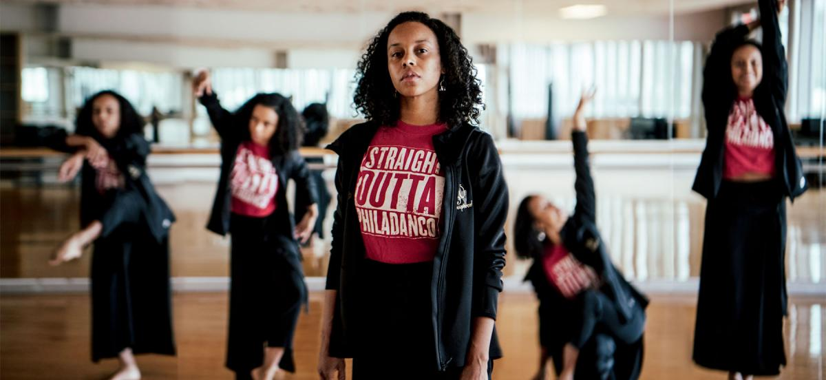 """Dana Nichols, wearing a """"Straight Outta Philadanco"""" tshirt, stands in a dance studio with dancers and a mirror behind her."""